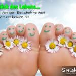 Füße mit lachenden Gesichtern daraufgemalt und Gänseblümchen zwischen den Zehen