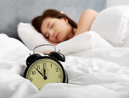 Frau schläft im Bett, im Verdergrund ist ein Wecker zu sehen