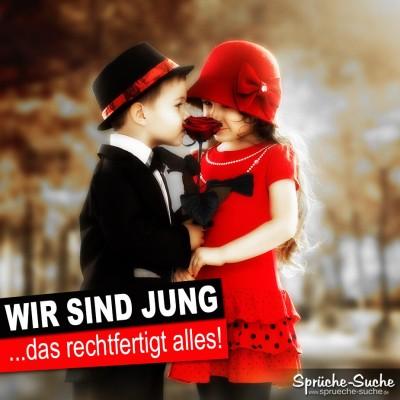 Junge im schwarzen Anzug küsst Mädchen im roten Kleid. Er hat eine Rose in der Hand.