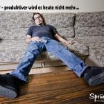 Mann liegt faul auf dem Sofa - die Füße liegen auf dem Tisch