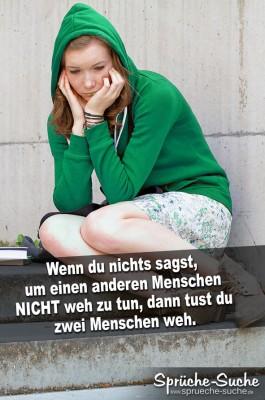 Sehr traurige und verzweifelte junge Frau mit grünen Pullover sitzt nachdenklich auf Treppe