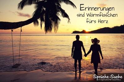 Paar steht am Strand und schaut sich den Sonnenuntergang an