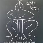 Lustige Froschzeichnung mit Kreide auf Tafel geschrieben