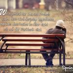 Mann mit Wollmütze sitzt alleine auf Parkbank