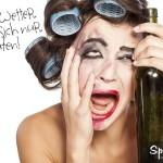 Betrunkene Frau mit Lockenwicklern im Haar und leerer Flasche in der Hand