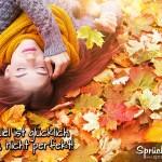 Glückliche Frau badet im Herbstlaub