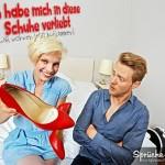 Frau hält freudestrahlend ihre nuen roten Schuhe in der Hand Der Mann neben ihr kann es nicht glauben