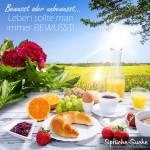 Reich gedeckter Frühstückstisch im Freien bei Sonnenschein - Spruch