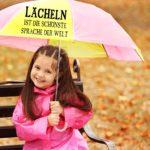 Kind mit Regenschirm lächelt in die Kamera - Spruchbild