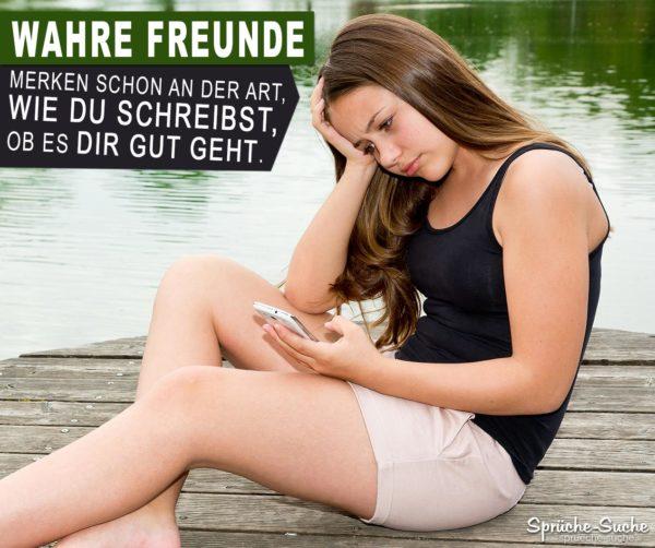 Wahre Freunde | Junge Frau nachdenklich am Steg mit einem Handy in der Hand als Spruchbild für wahre Freundschaft
