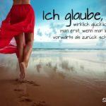 Sprüche über Glück - Frau im leichten roten Kleid spazierend am Strand