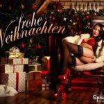 Erotische Weihnachtsgrüße: Halbnackte Frau mit Strapsen im Weihnachtsoutfit