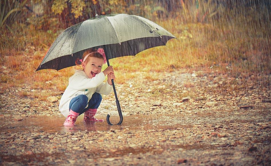 Kind in Pfütze mit grünen Regenschirm in der Hand