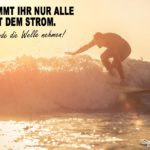 Mit dem Strom schwimmen - Surfer auf einer Welle bei Sonnenuntergang