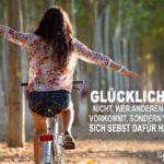Glückliches Mädchen freihändig auf dem Fahrrad fährt durch Allee