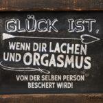 Glück ist Lachen und Orgasmus - Spruch auf Tafel mit Holzumrandung
