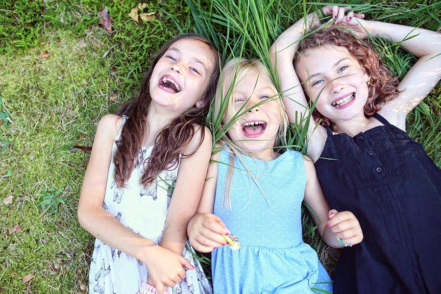 3 Kinder liegen freudestrahlen auf der Wiese