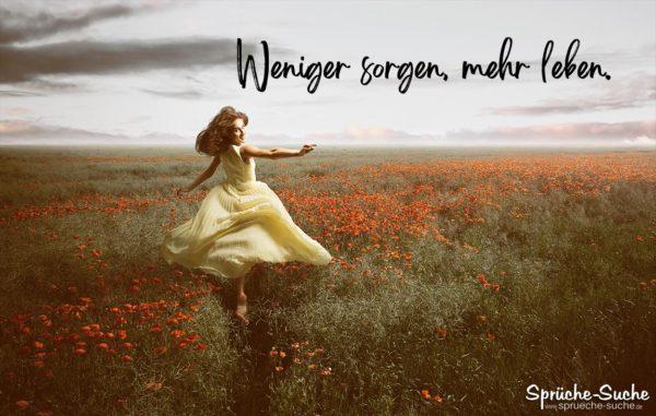 Fröhliche Frau im Feld - Weniger sorgen, mehr leben Spruch